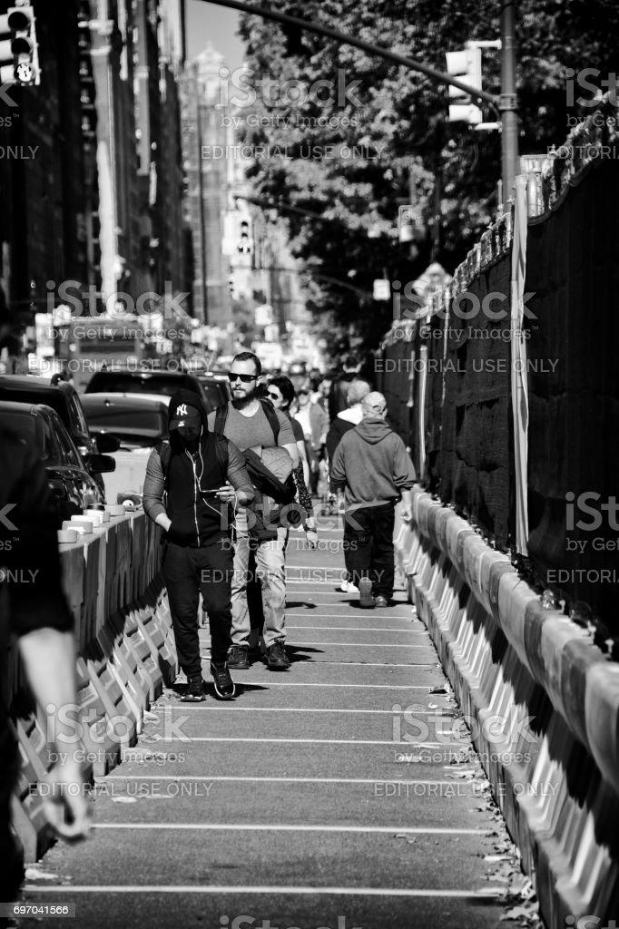 Urban Life, New York City. Pedestrians walking past construction barriers along Central Park West, Manhattan. stock photo