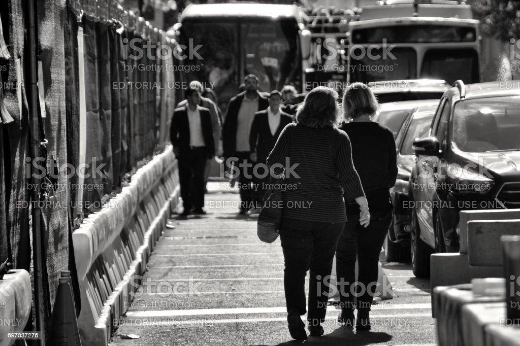 Urban Life, New York City. Pedestrians walking past construction barriers in Manhattan stock photo