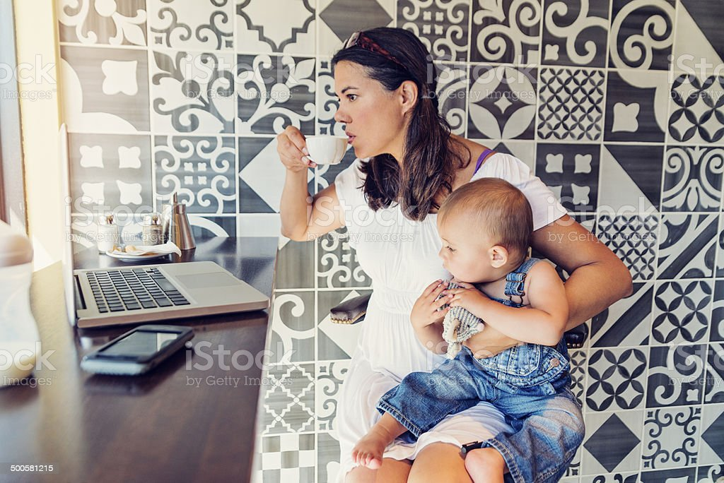 Urban mom balancing work and family in a public cafe. stock photo