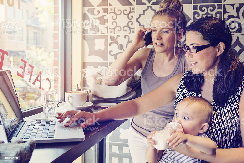 Urban mom balancing work and family with colleague in cafe. stock photo