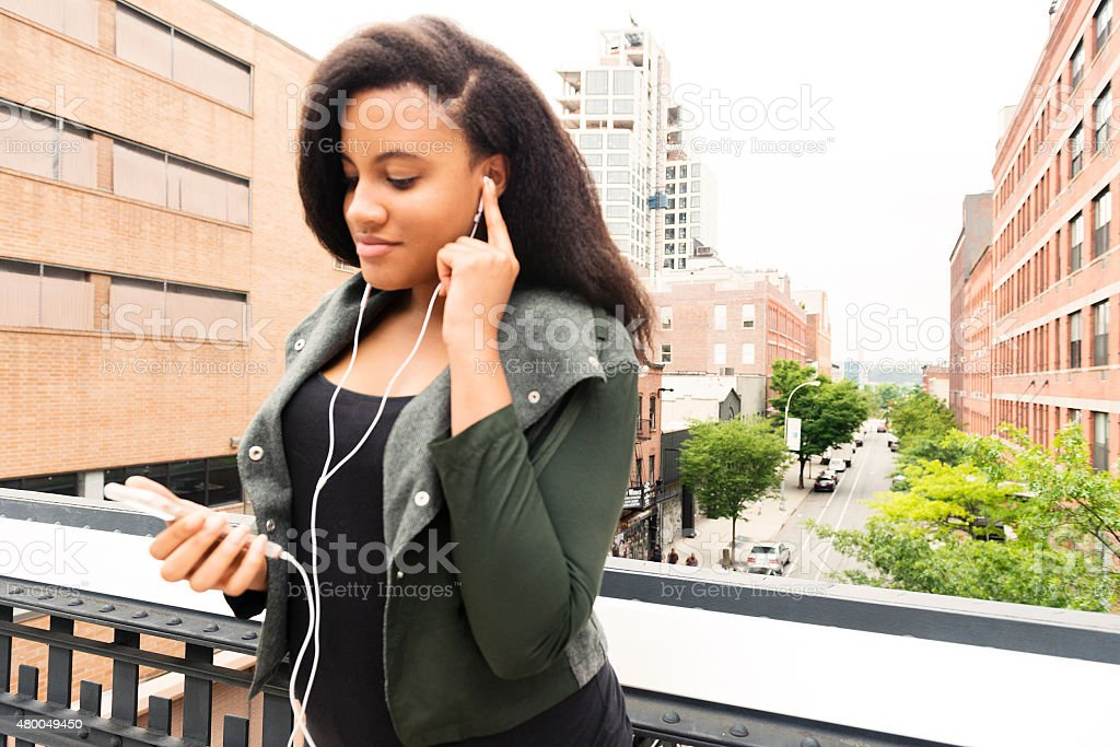 Urban NYC Woman Listening to Music Outdoors High Line Park stock photo