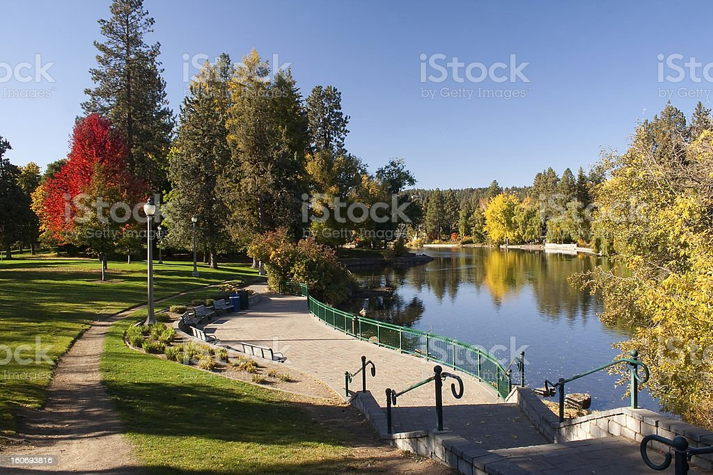 Urban park, lake and paved path with stairs stock photo