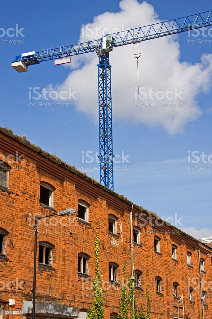 Urban regeneration in progress with derelict warehouse and tower crane stock photo
