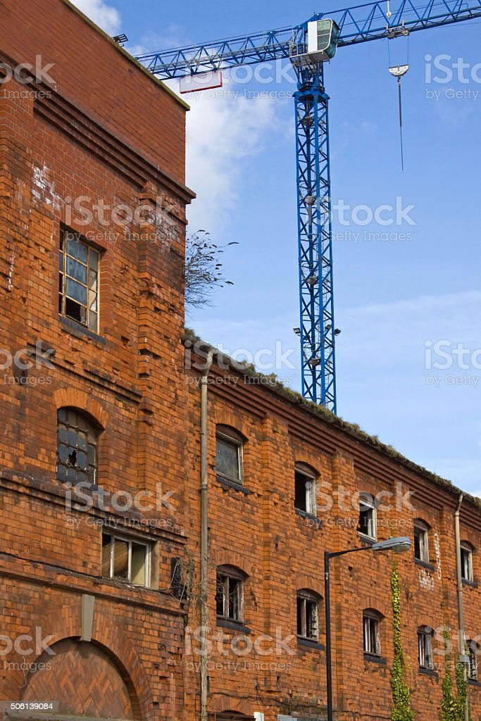 Urban regeneration site with derelict warehouse and tower crane UK stock photo