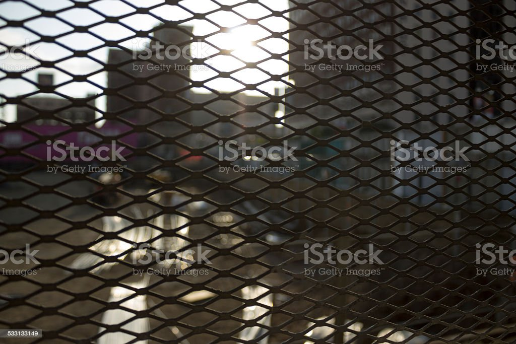 Urban Setting Through Metal Fence stock photo