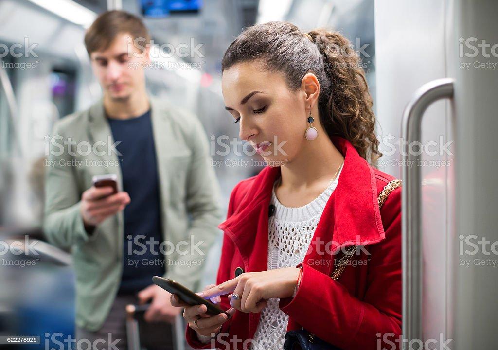 Urban transport scene: couple holding phones stock photo