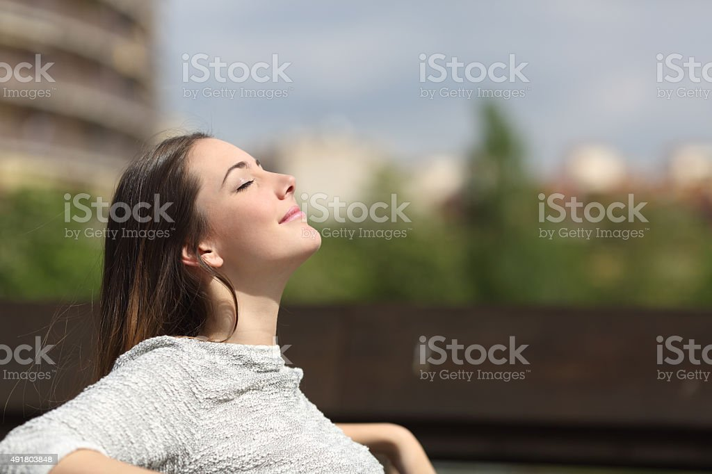 Urban woman breathing deep fresh air stock photo