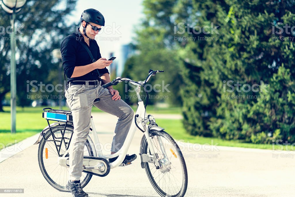 Urban young man with electric bicycle, using smart phone stock photo