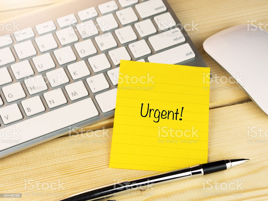Urgent on sticky note on work table stock photo