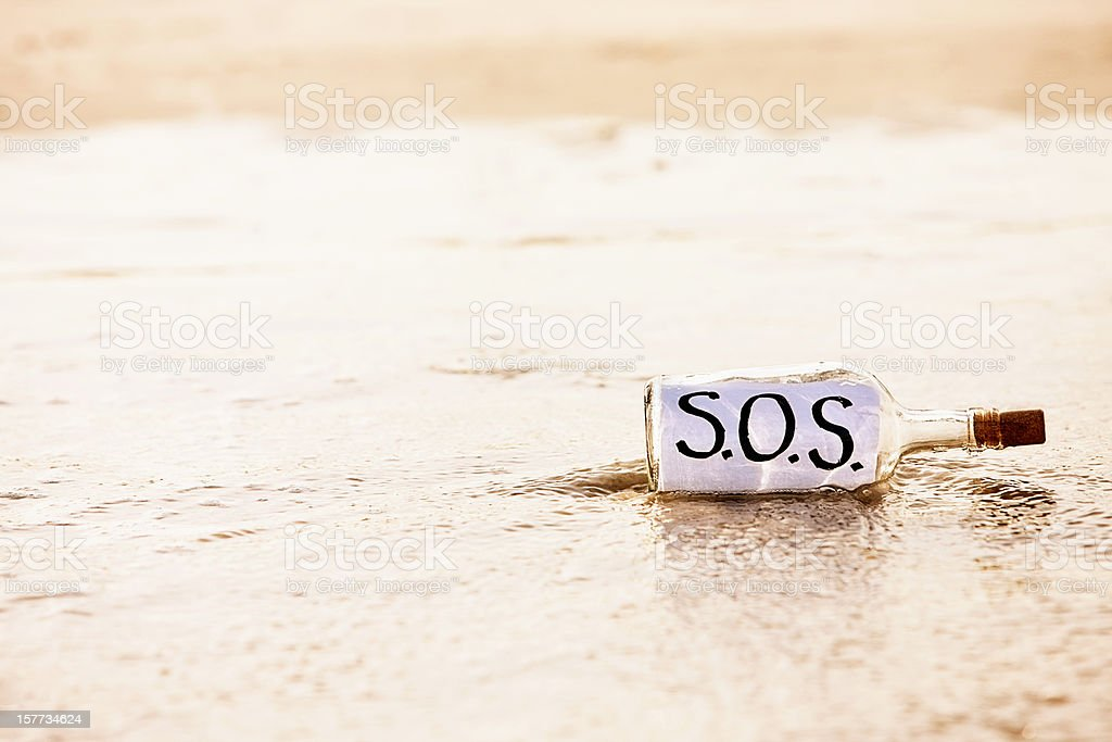 Urgent plea for help in washed-up bottle reads SOS royalty-free stock photo