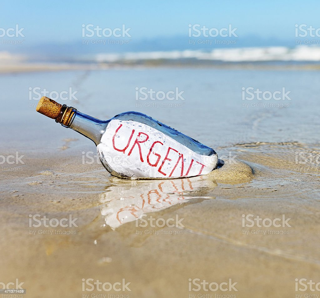 Urgent says message in bottle at water's edge stock photo