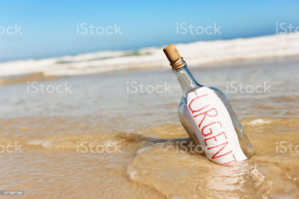 Urgent says message in bottle being swept away by tide stock photo