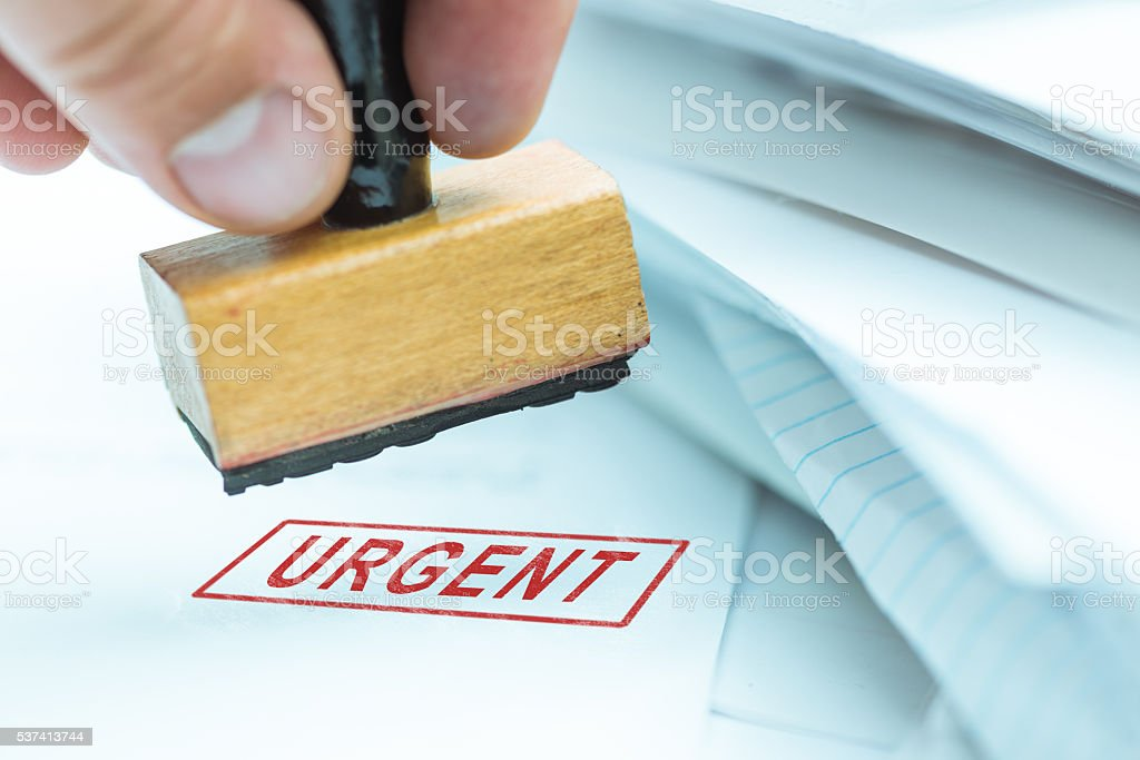 Urgent stamp on papers stock photo