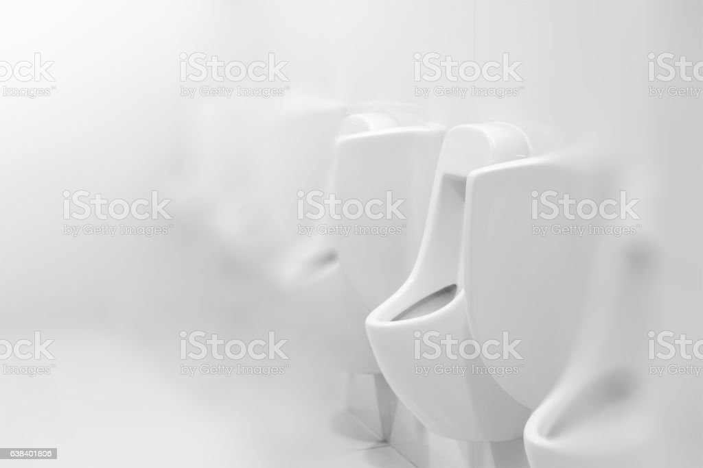 Urinals in white public toilet or restroom, interior design stock photo