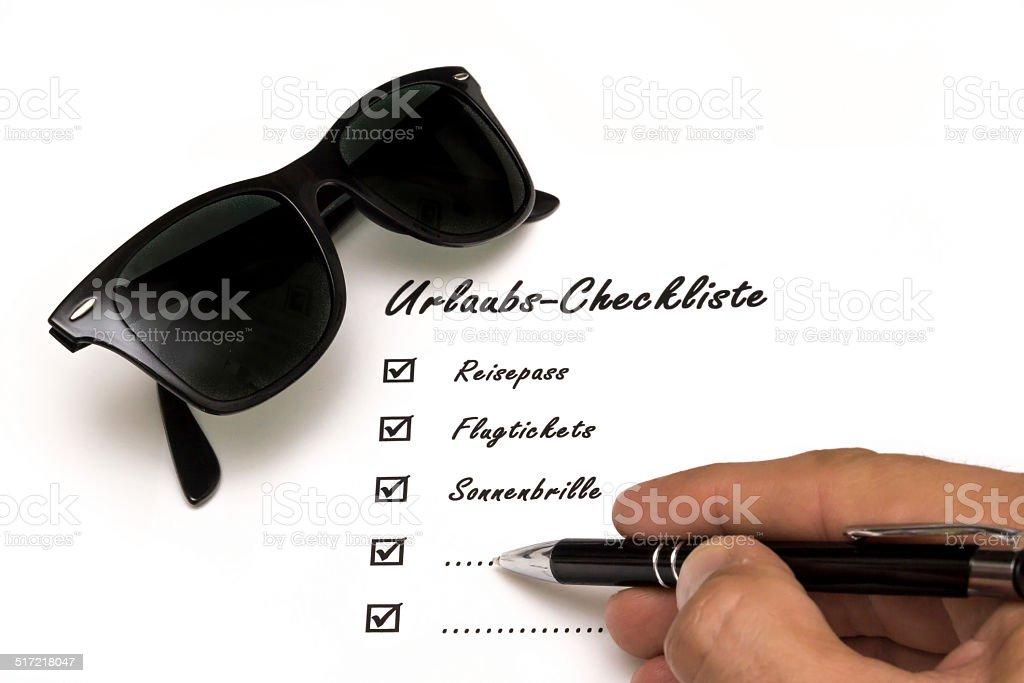 Urlaubs-Checkliste beim Ausf?llen mit Brille stock photo