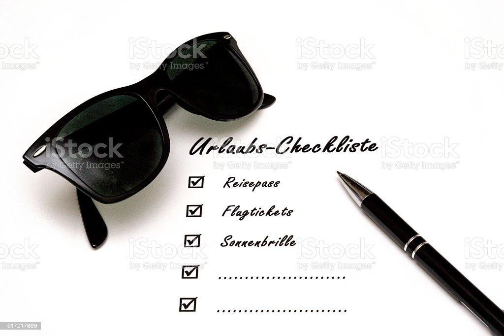 Urlaubs-Checkliste mit Stift und Sonnenbrille stock photo