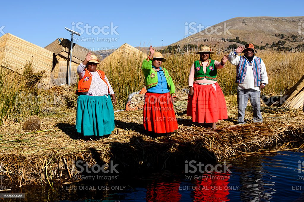 Uros indigenous people wearing traditional clothing on floating island stock photo