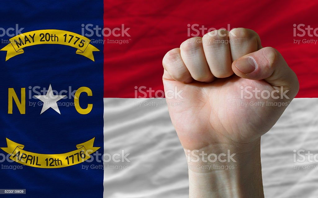 us state flag of north carolina with hard fist stock photo