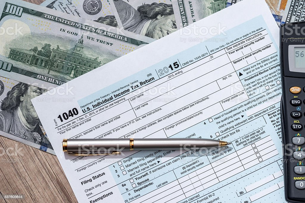 us tax foem with money, calculator and pen stock photo