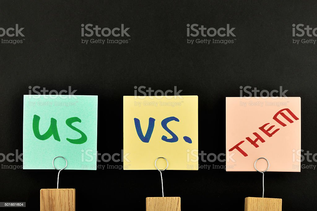 Us vs them three paper notes isolated on black royalty-free stock photo