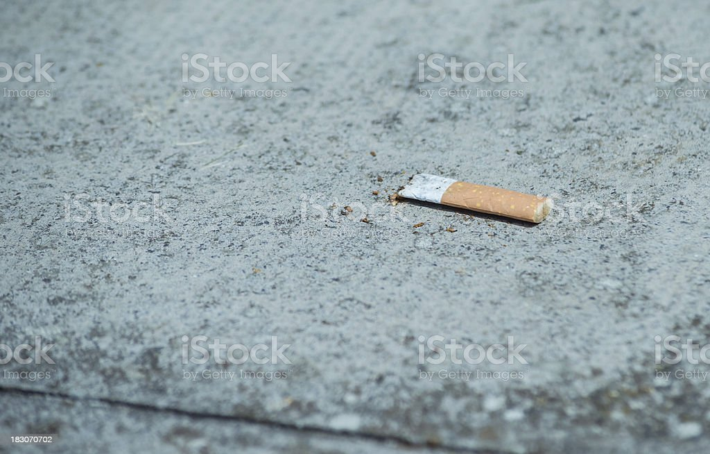Used and Crushed Cigarette Fliter on Pavement royalty-free stock photo