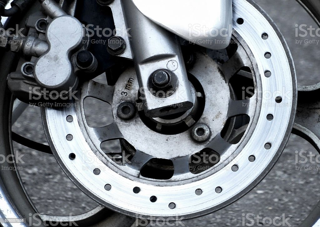 Used brake rotor and support plate on the motorcycle stock photo