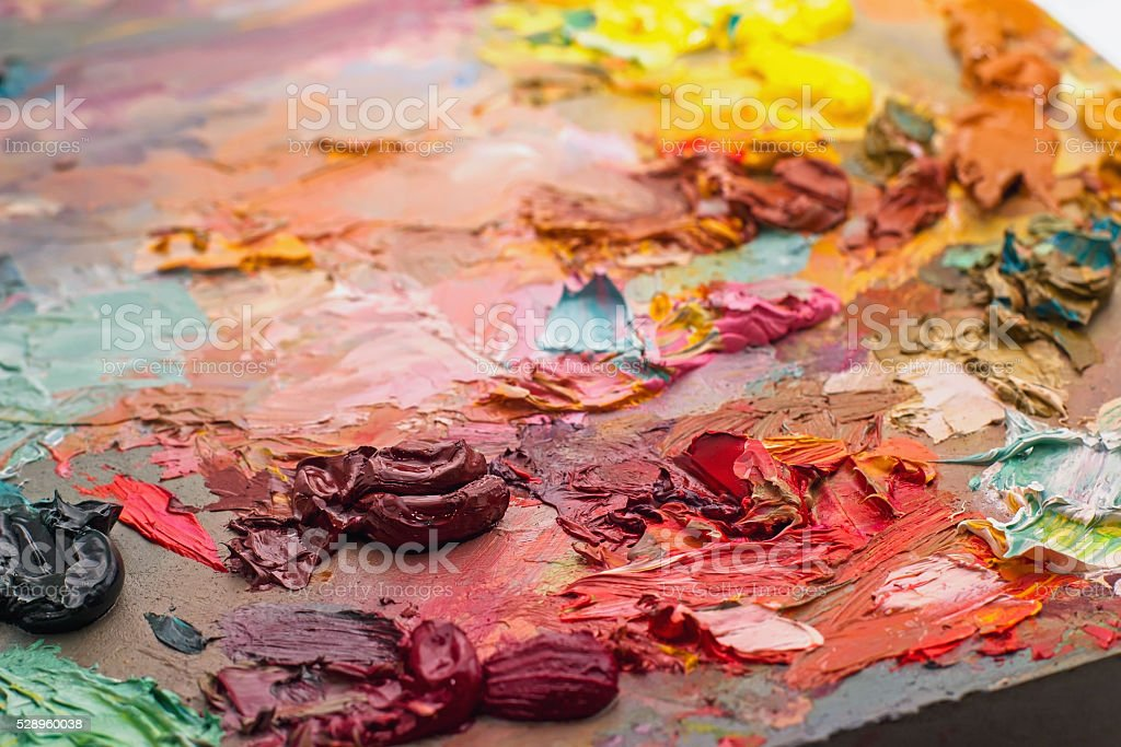 used brushes in an artist's palette of colorful oil paint stock photo