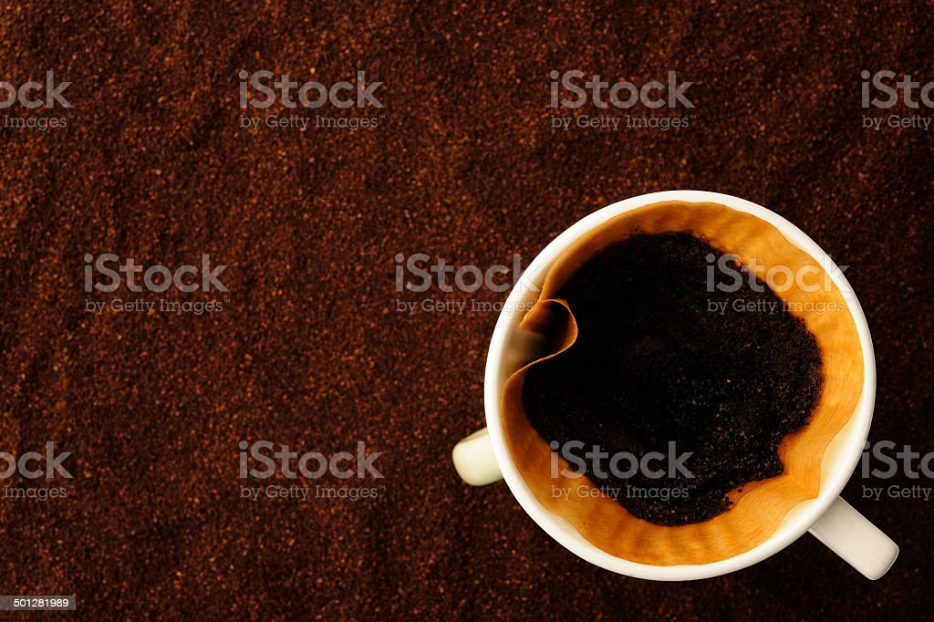 Used coffee filter with coffee cup on ground coffee beans royalty-free stock photo