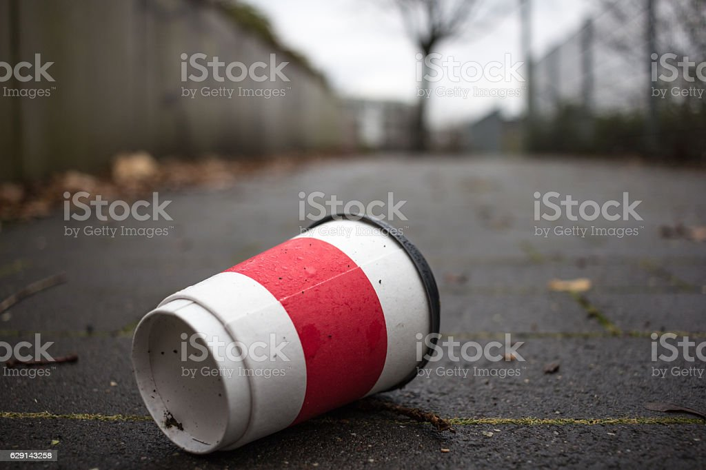 Used Coffee mug at sidwalk as symbol for pollution. stock photo