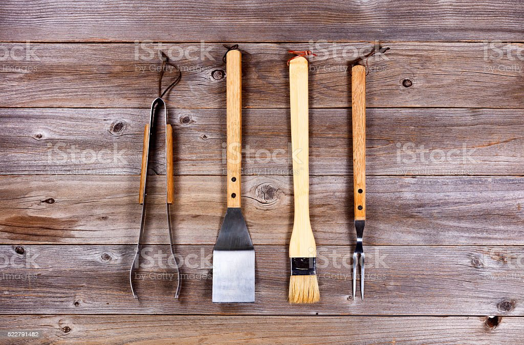 Used kitchenware for barbecue cooking on rustic wood stock photo
