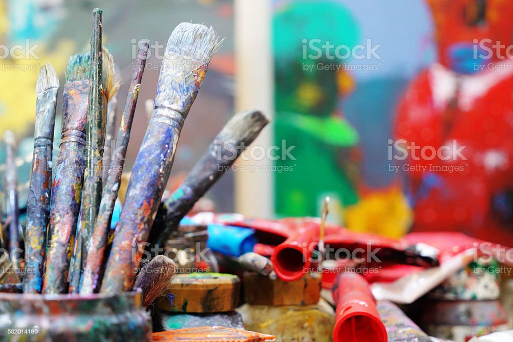 used paint brushes on a colorful painter palette stock photo