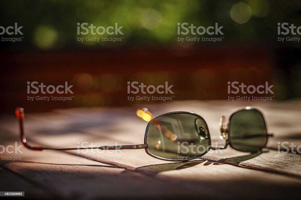 Used sunglasses on wooden table in spot of sunlight. stock photo