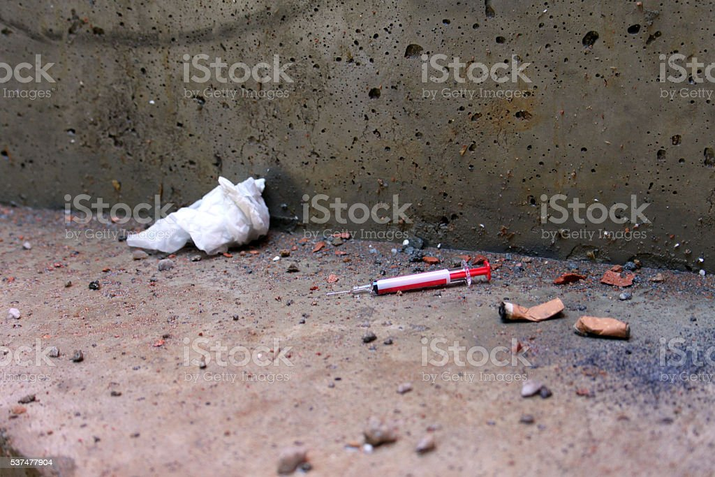 Used syringe thrown down with cigarette butts. Concrete dirt floor stock photo