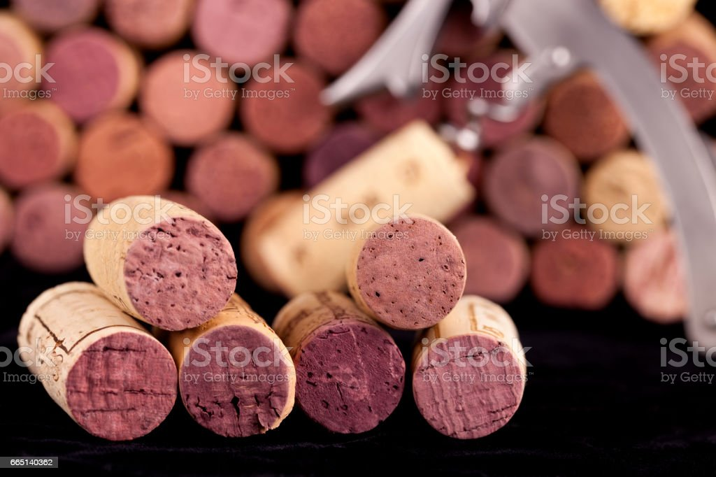 Used wine corks with corkscrew sitting on a black towel stock photo