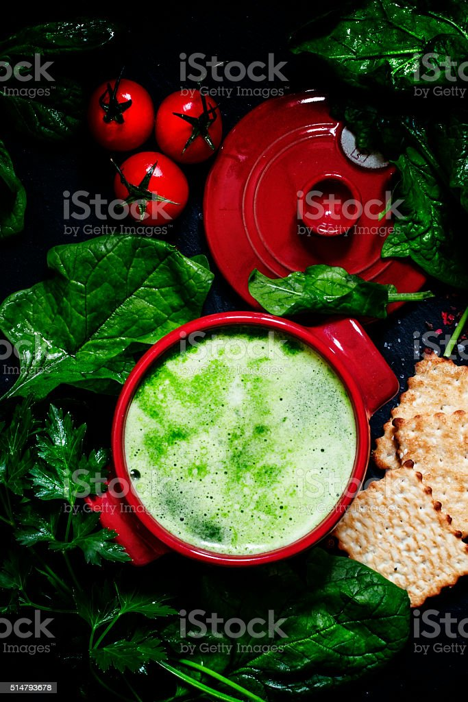 Useful healthy spinach soup in red saucepan stock photo