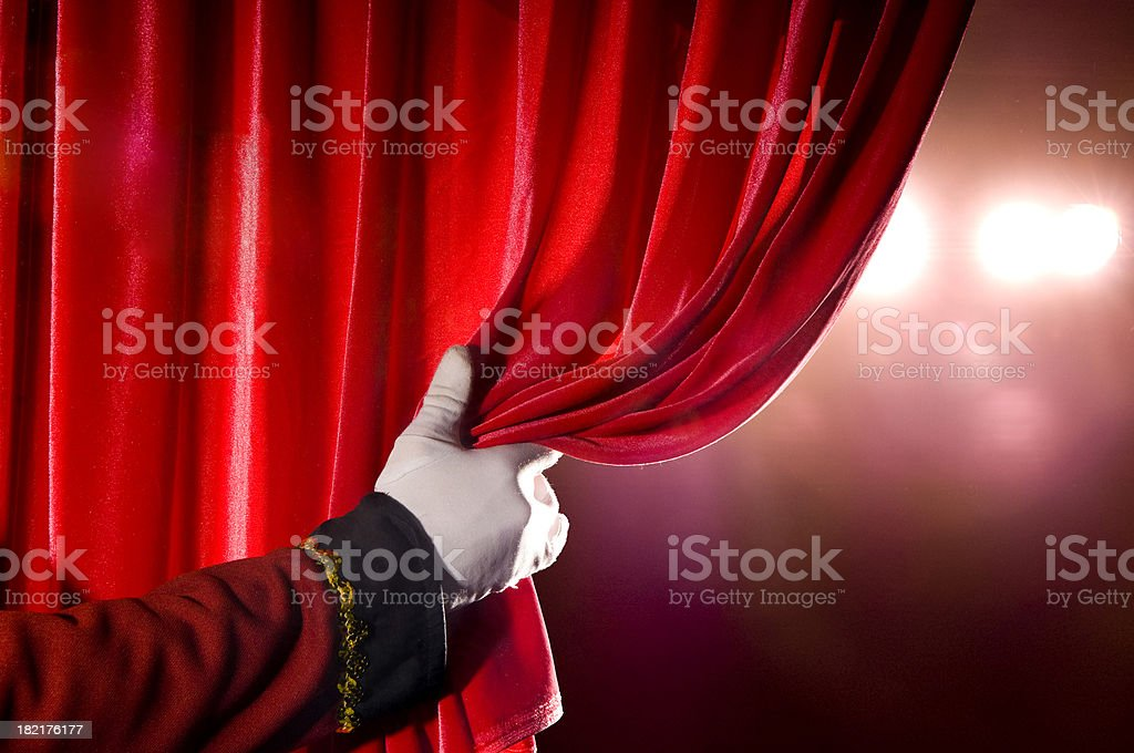 Usher opening red theater curtain, with spotlights stock photo