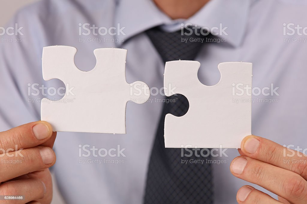 usinessman holding two pieces of a blank puzzle stock photo