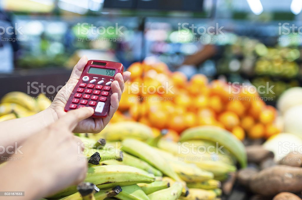 Using a calculator at the supermarket stock photo