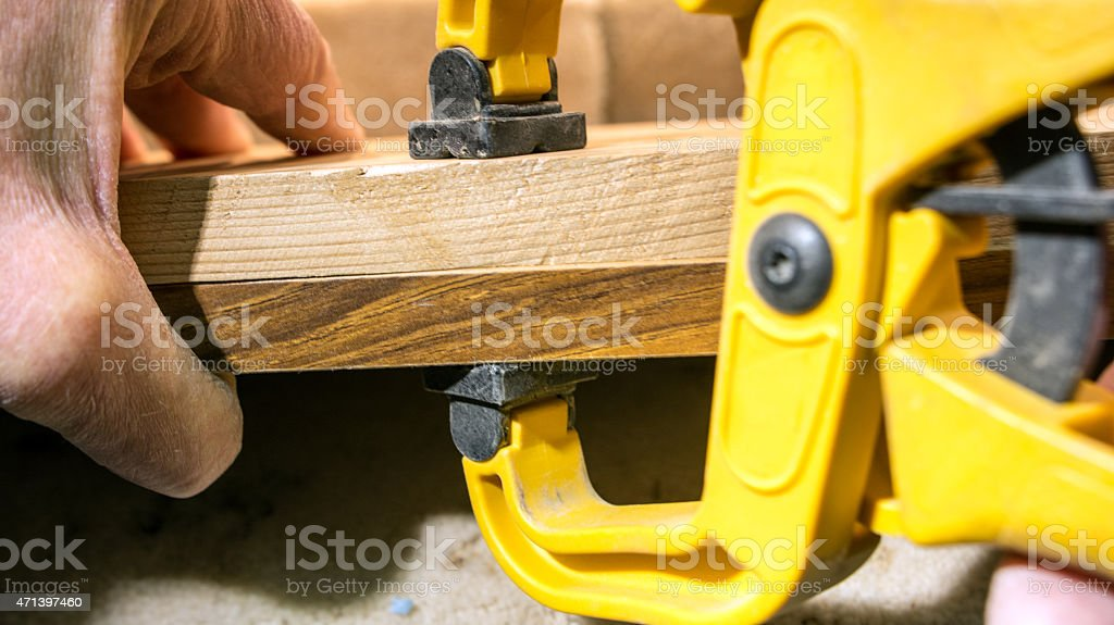DIY- using a  clamp to attach  pieces of glued wood stock photo