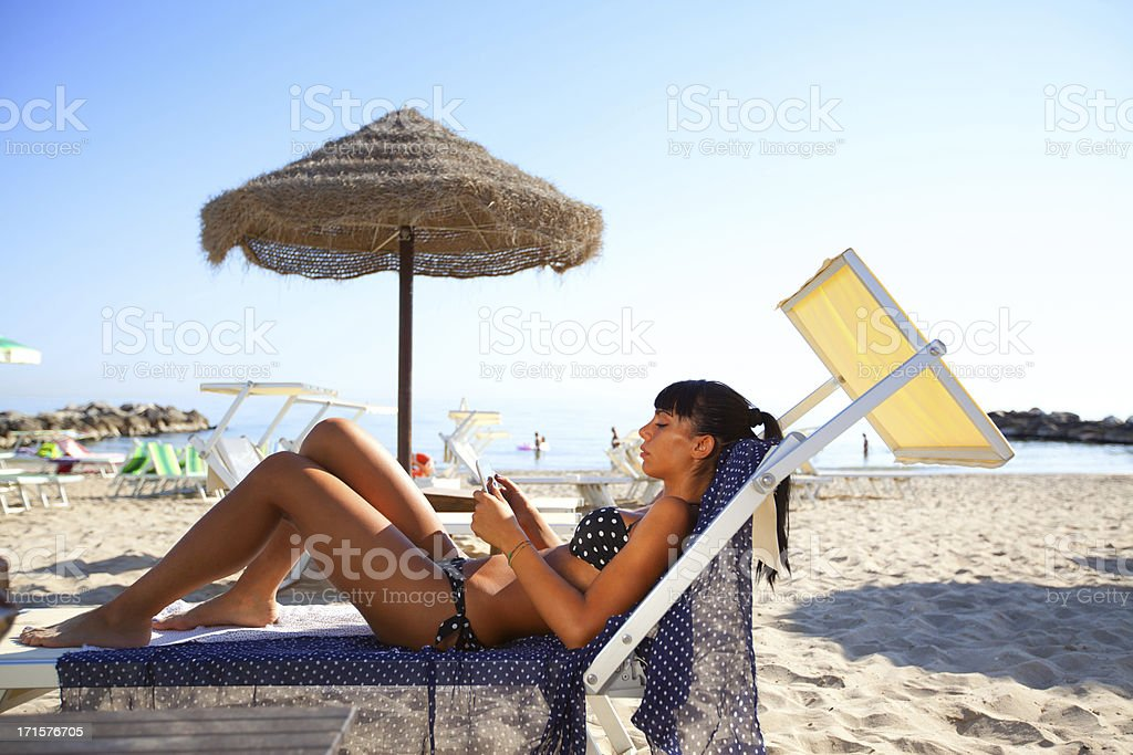 Using a digital tablet at the beach royalty-free stock photo
