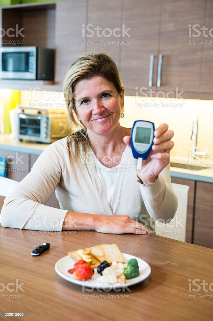 Using a glaucometer to monitor diabetes stock photo