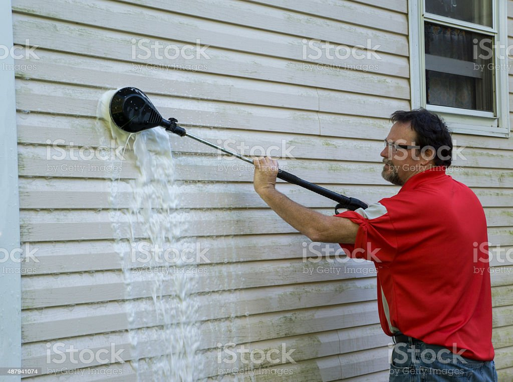 Using A High Pressure Brush To Clean Algae And Mold stock photo