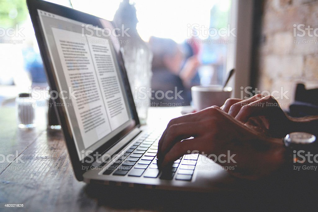 using a laptop in a cafe stock photo