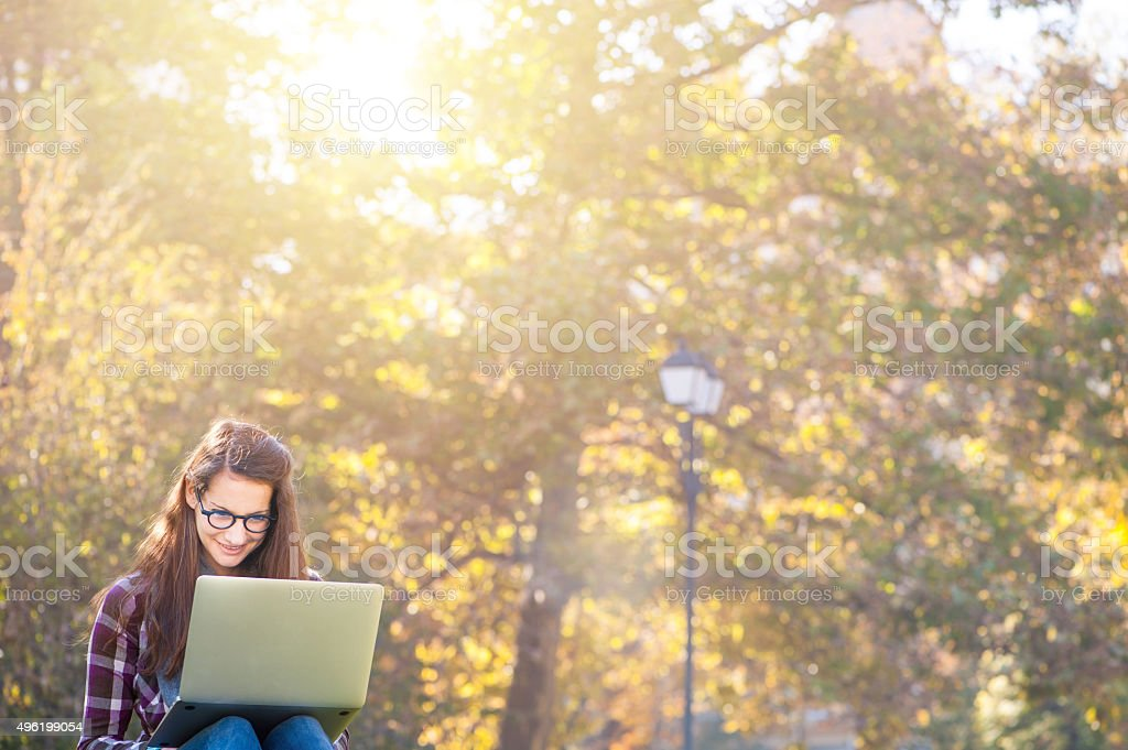 Using a laptop outdoors stock photo