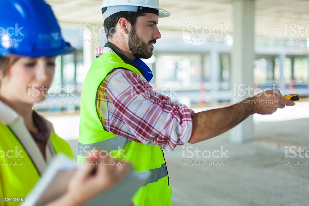 Using a lasere distant meter on a construction site. stock photo