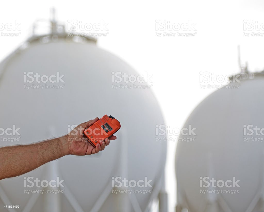Using a Leak Detector near Gas storage tanks stock photo