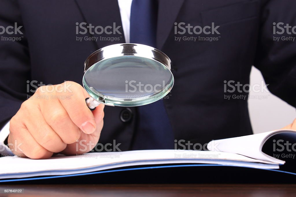 Using a magnifying glass stock photo