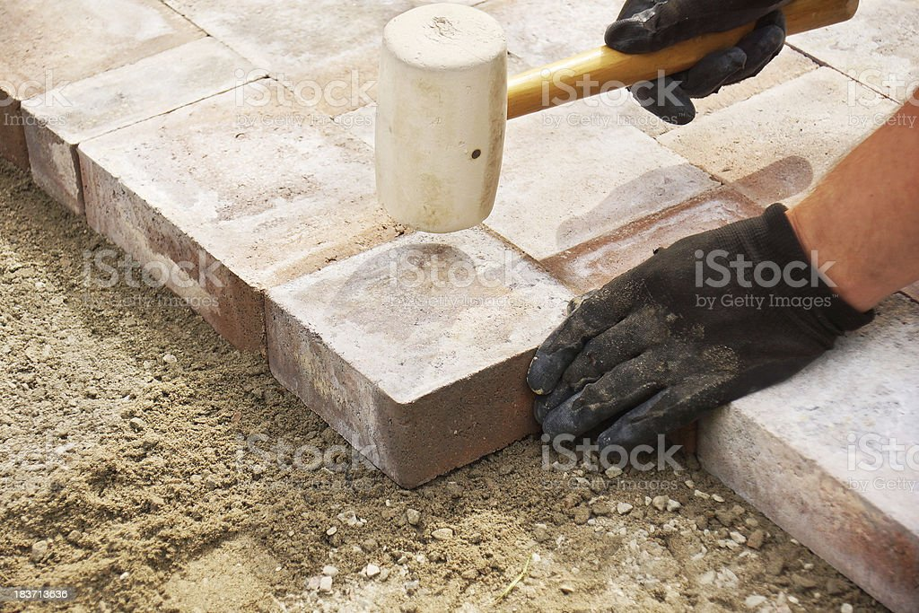 Using a mallet to set paver stock photo