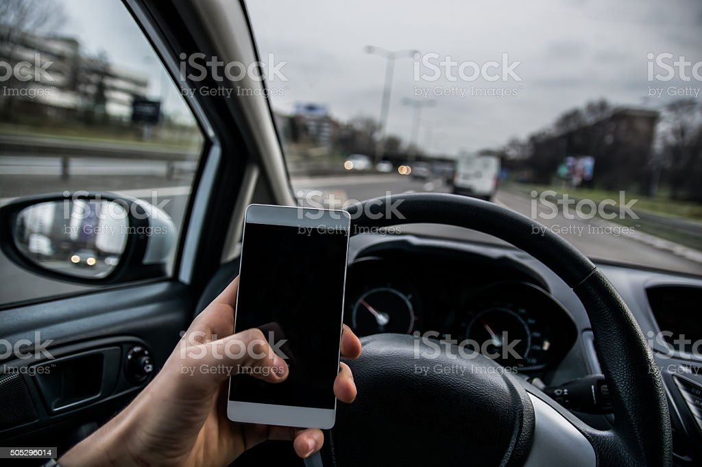 Using a phone while driving a car stock photo