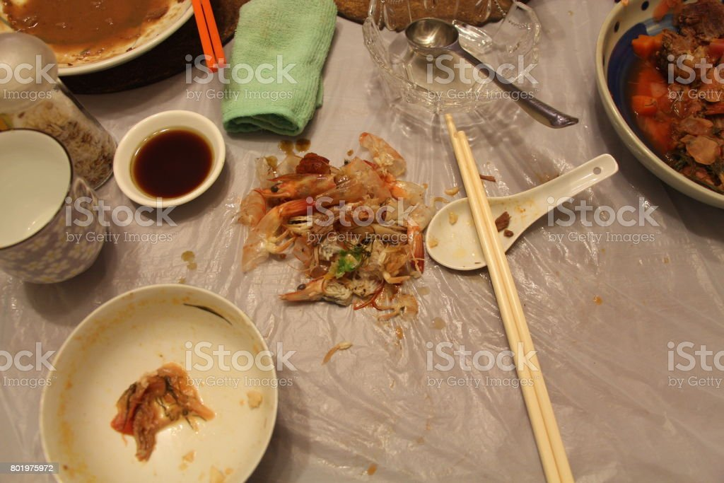 Using a plastic sheet instead of tablecloth, dumping prawn shells onto it stock photo